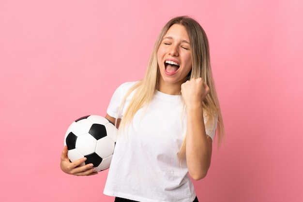 Young blonde woman isolated on pink wall with soccer ball celebrating a victory