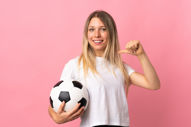 Young blonde woman isolated on pink wall with soccer ball and proud of herself