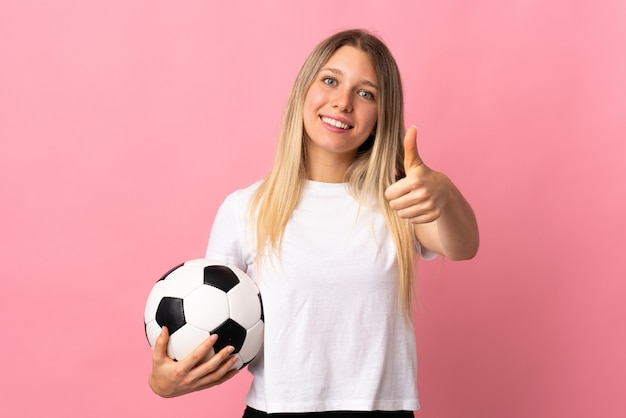 Young blonde woman isolated on pink wall with soccer ball and with thumb up