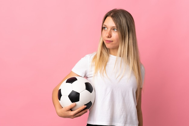 Young blonde woman isolated on pink wall with soccer ball