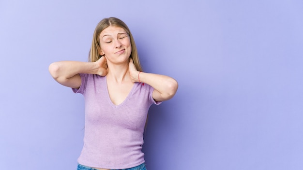 Young blonde woman isolated on purple background suffering neck pain due to sedentary lifestyle.
