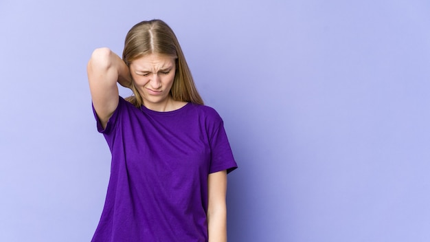 Young blonde woman isolated on purple wall suffering neck pain due to sedentary lifestyle.