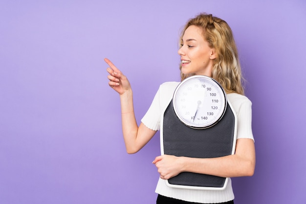 Young blonde woman isolated on purple wall with weighing machine and pointing side
