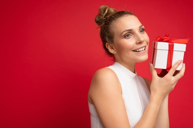 Young blonde woman isolated over red background wall wearing white top holding gift box and looking to the side. copy space, mockup