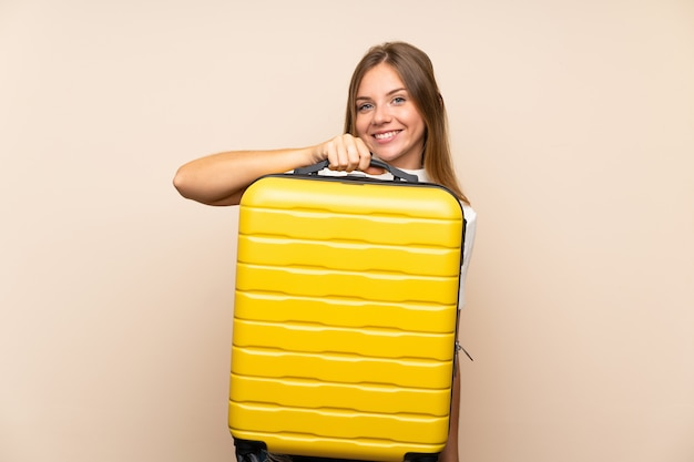 Young blonde woman over isolated wall holding a vintage briefcase