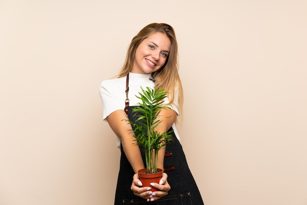 Young blonde woman over isolated wall taking a flowerpot
