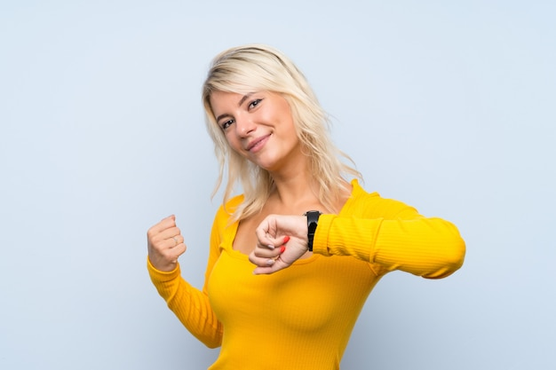Young blonde woman over isolated wall with wrist watch and lucky expression