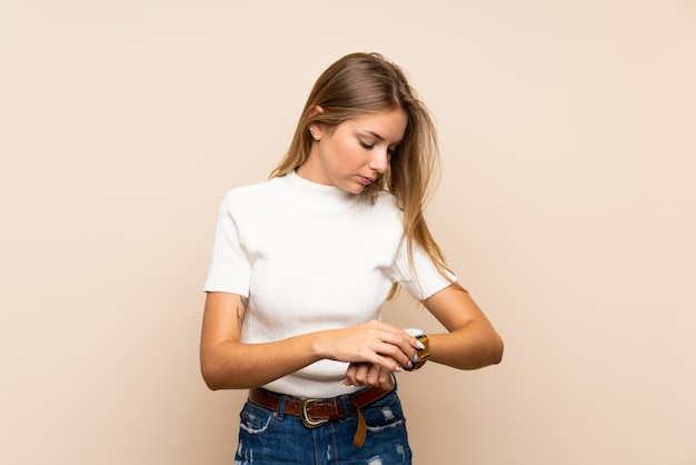 Young blonde woman over isolated wall with wrist watch