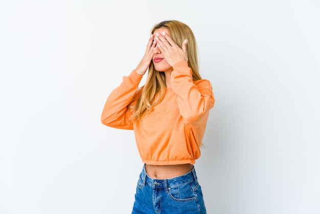 Young blonde woman isolated on white background afraid covering eyes with hands.