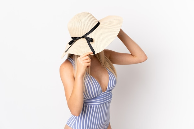 Young blonde woman isolated on white background in swimsuit in summer holidays
