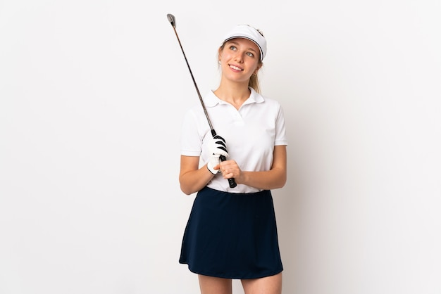 Young blonde woman isolated on white wall playing golf and looking up while smiling