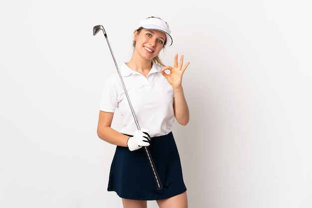 Young blonde woman isolated on white wall playing golf making ok sign