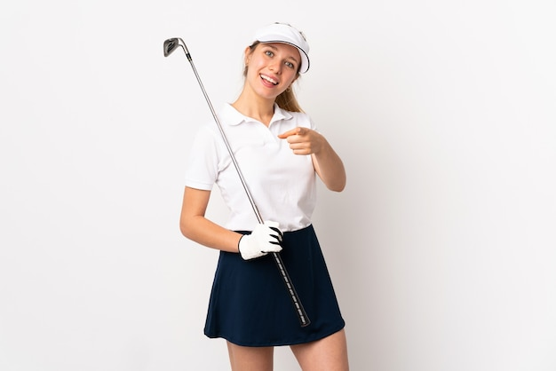 Young blonde woman isolated on white wall playing golf and pointing to the front