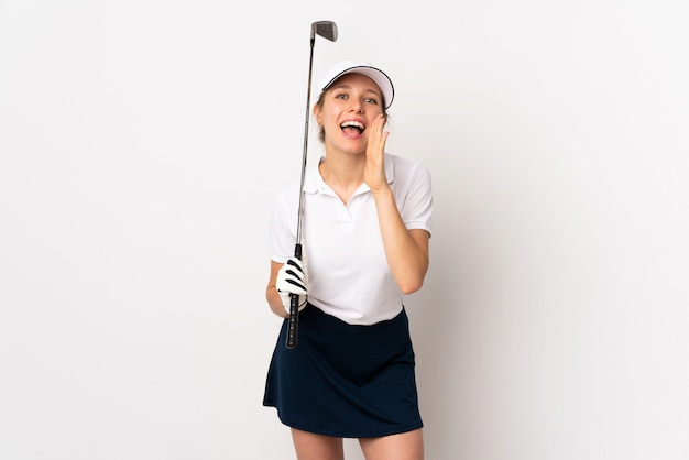 Young blonde woman isolated on white wall playing golf and shouting with mouth wide open