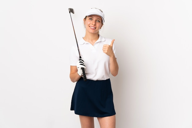 Young blonde woman isolated on white wall playing golf and with thumbs up because something good has happened