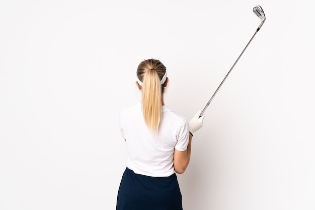 Young blonde woman isolated on white wall playing golf