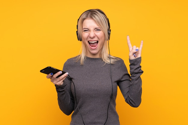 Young blonde woman over isolated yellow wall listening music with a mobile making rock gesture