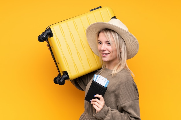 Young blonde woman over isolated yellow wall in vacation with suitcase and passport