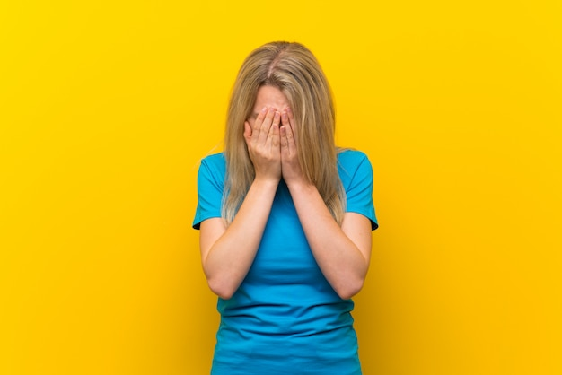 Young blonde woman over isolated yellow with tired and sick expression