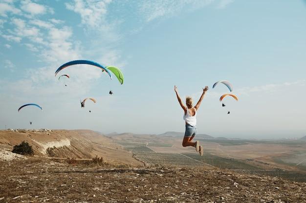 丘の上にジャンプする若いブロンドの女性