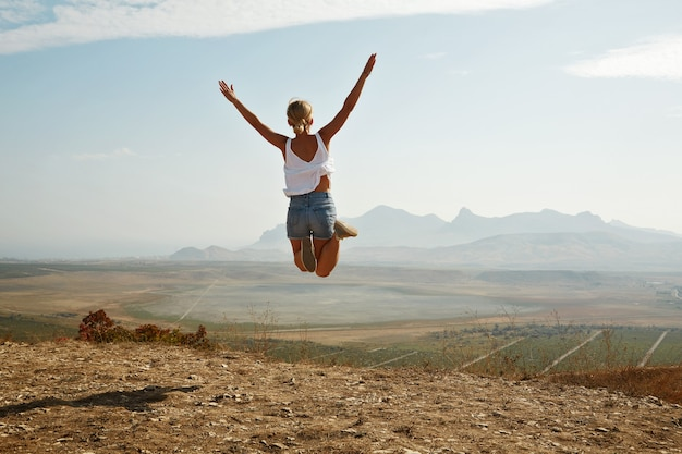 Young blonde woman jumping on top of hill