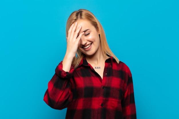 Молодая блондинка смеется и хлопает по лбу, как будто говоря: «о! я забыл или это была глупая ошибка
