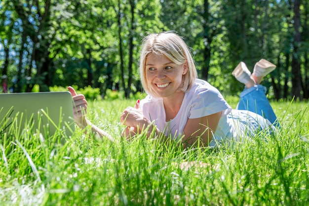 Young blonde woman lies in a park on the grass with a laptop. blogging, education and remote work.