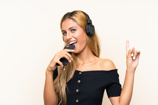 Young blonde woman listening music with a mobile and singing over isolated wall