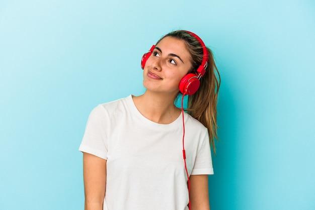 目標と目的を達成することを夢見て青い背景に分離されたヘッドフォンで音楽を聞いている若いブロンドの女性