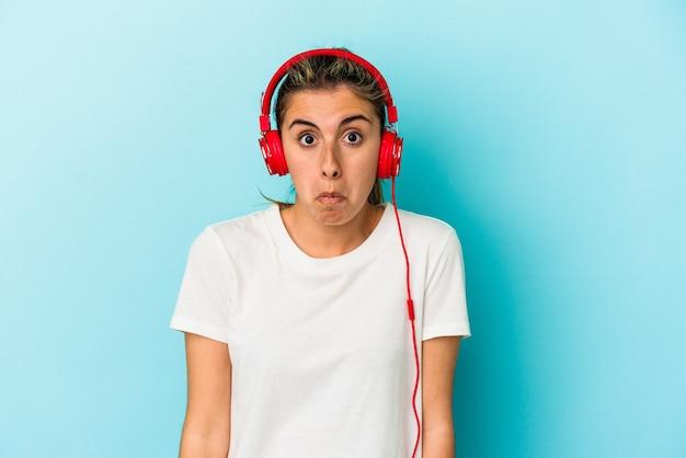 青い背景に分離されたヘッドフォンで音楽を聴いている若いブロンドの女性は肩をすくめると混乱した目を開いています。