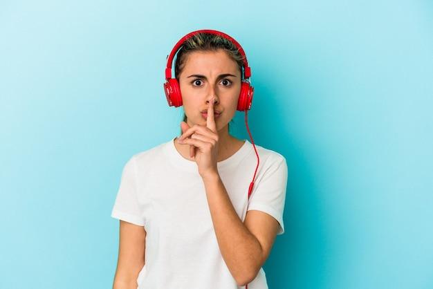 秘密を保持するか、沈黙を求めて青い壁に分離されたヘッドフォンで音楽を聞いている若いブロンドの女性