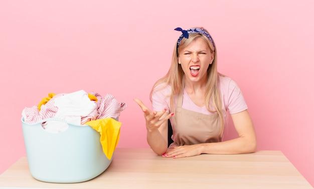 Молодая блондинка выглядит сердитой, раздраженной и разочарованной. концепция стирки одежды