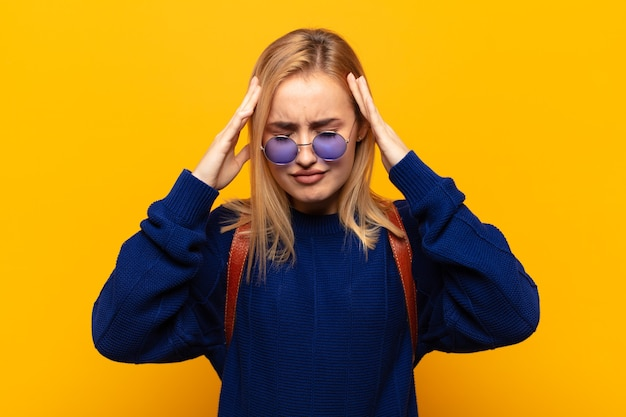 Young blonde woman looking concentrated, thoughtful and inspired, brainstorming and imagining with hands on forehead