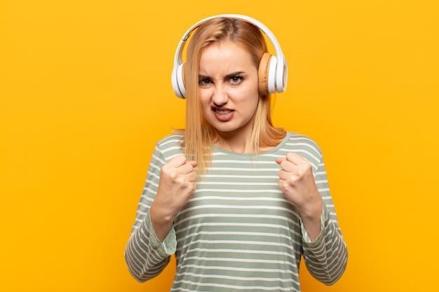 Молодая блондинка выглядит уверенной, злой, сильной и агрессивной, с кулаками, готовой к бою в боксерской позе