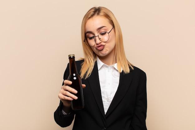 Молодая блондинка выглядит глупо и забавно с глупым косоглазым выражением лица, шутит и дурачится