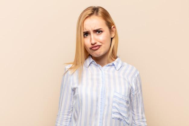 愚かな斜視の表情で間抜けで面白いように見える若いブロンドの女性は、冗談を言ったり、浮気したりします