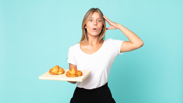 Young blonde woman looking happy, astonished and surprised and holding a croissant tray