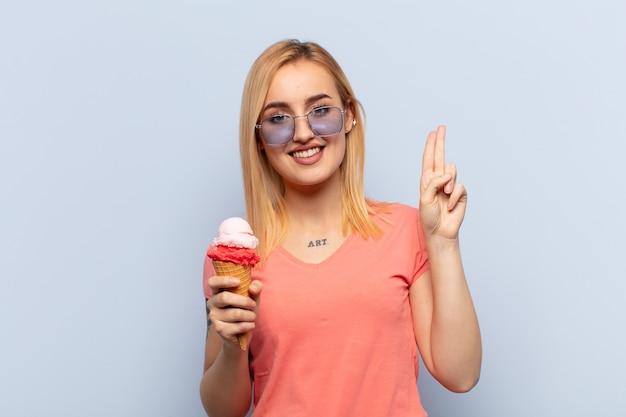 Молодая блондинка выглядит счастливой, уверенной и заслуживающей доверия, улыбается и показывает знак победы, с позитивным настроем