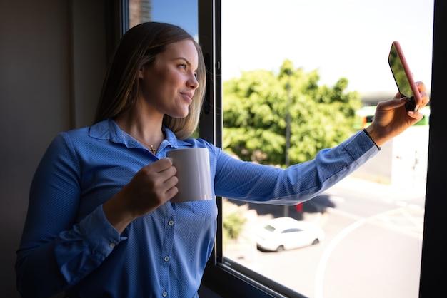 커피를 마시고 화상 통화를 하는 동안 창 밖을 바라보는 젊은 금발의 여자