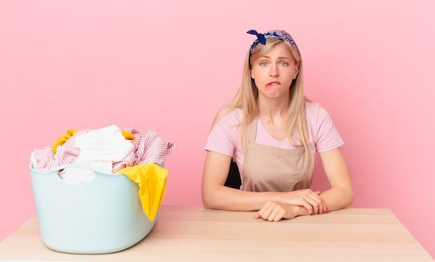 Молодая блондинка выглядит озадаченно и смущенно. концепция стирки одежды