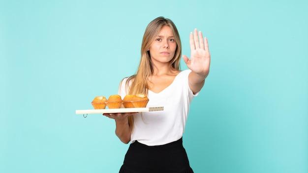 Молодая блондинка выглядит серьезно, показывая открытую ладонь, делая стоп-жест и держа тройню кексов