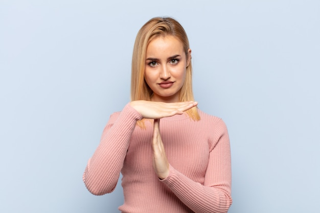 Young blonde woman looking serious, stern, angry and displeased, making time out sign
