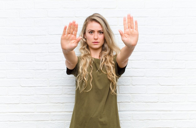 Young blonde woman looking serious, unhappy, angry and displeased forbidding entry or saying stop with both open palms against brick wall