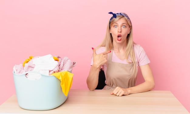 Молодая блондинка выглядит потрясенной и удивленной с широко открытым ртом, указывая на себя. концепция стирки одежды