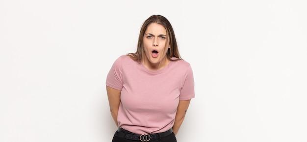 ショックを受けた、怒っている、イライラした、または失望した、口を開けて激怒しているように見える若いブロンドの女性