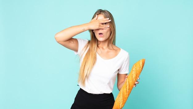 ショックを受けたり、怖がったり、恐怖を感じたり、手で顔を覆ったり、パンのバゲットを持っている若いブロンドの女性