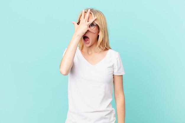 Молодая блондинка выглядит шокированной, напуганной или напуганной, закрывая лицо рукой