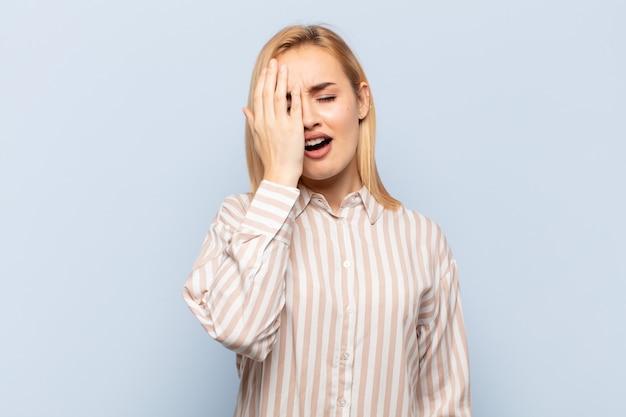頭痛と片方の手が顔の半分を覆っている、眠くて退屈であくびをしている若いブロンドの女性