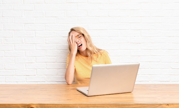 Young blonde woman looking sleepy, bored and yawning, with a headache and one hand covering half the face using a laptop