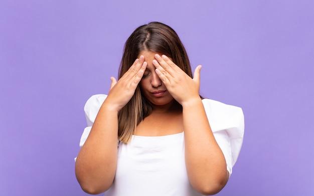 스트레스와 좌절을 찾고 젊은 금발의 여자는 두통으로 압력을 받고 문제로 고민하고 있습니다. 프리미엄 사진